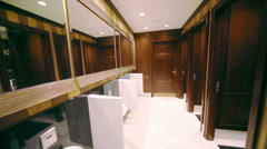Interior of public men room with urinals and wooden finishing Stock Footage