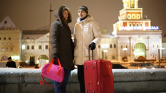 Man and woman stand with big bag, talk and look at watch Stock Footage