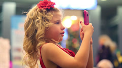 Blonde little cute girl plays with pink cell phone and talks - stock footage