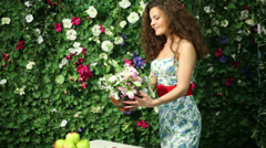 Beautiful woman puts bunch of flowers on table next to hedge Stock Footage