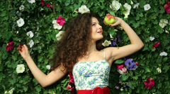 Beautiful happy woman with apple next to green hedge in garden Stock Footage