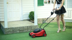 Legs of housemaid mowing lawn by lawnmower near country house Stock Footage