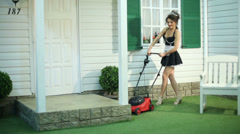 Smiling housemaid mows lawn by lawnmower near country house Stock Footage