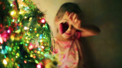 Pretty girl decorates Christmas tree by toy heart at evening Stock Footage
