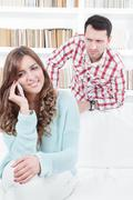 Jealous worried man peering over the shoulder of his girlfriend Stock Photos