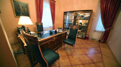 Leather chairs and gilt table with lamp in home office Stock Footage