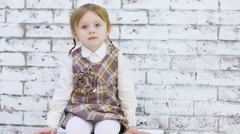 Little beautiful girl sits next to brick white wall in studio Stock Footage