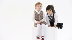 Little girl sits on white big cube and little boy dismount cube Stock Footage