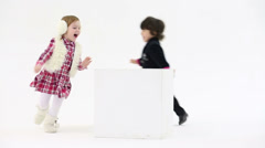 Little pretty boy and girl run around large cube in white studio - stock footage