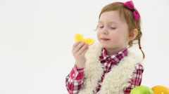 Little beautiful girl eats piece of orange and smiles in studio Stock Footage