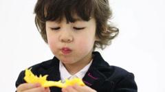Little cute boy in coat eats orange in white studio Stock Footage