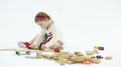 Little cute girl plays with wooden toy railroad in white studio Stock Footage