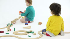 Little boy and girl play with wooden toy railroad in studio Stock Footage
