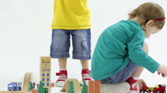 Little boy and sitting girl play with wooden toy railroad Stock Footage