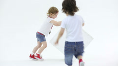 Little girl and boy in shorts with medal plays with big cube Stock Footage