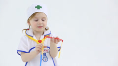 Little girl plays with toy red glasses and medical instruments - stock footage