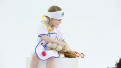 Little boy and girl play with toy medical instruments - stock footage