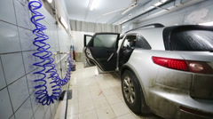 Dirty and wet grey car stands in workshop of Service station Stock Footage