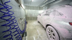 Dirty and wet car in foam stands in workshop of Service station Stock Footage