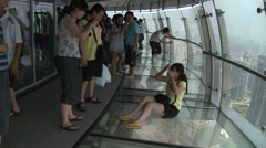 Scary shot. Girls sits on glass floor of tower - pan down - stock footage