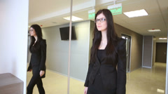 Woman in suit goes in waiting hall of business center Stock Footage