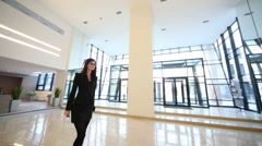 Woman in suit goes near glass door in hall of business center Stock Footage