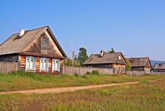 Row of traditional wooden houses in a remote village in russian siberia Stock Photos