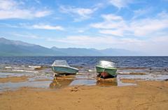 Two rusty motor boats at anchor on the beach at the shores of lake baikal Stock Photos