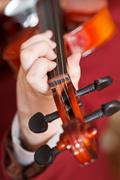 Girl plays on fiddle - chord on fingerboard Stock Photos