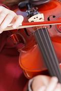 Girl playing fiddle - violin strings and bow Stock Photos