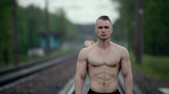 Muscular strong man stands on railroad tracks Stock Footage