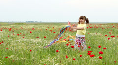 Little girl waving with colorfu ribbons on meadow Stock Footage