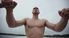 Muscular strong man row of old boat, floating on a boat with oars. Slow motion. Stock Footage