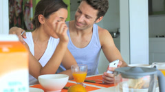 couple looking at internet while having breakfast - stock footage