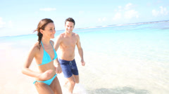 Couple running on a sandy beach Stock Footage