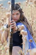 fairytale girl with bow and arrow - stock photo