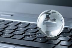 glass globe on laptop keyboard - stock photo