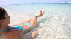 Young woman relaxing in transparent water Stock Footage