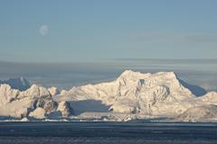 low antarctic mountain on which the moon is visible. - stock photo