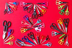 Random groups of multiple scissors conceptualy laid on red Stock Photos