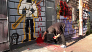 Stock Video Footage of Street artist is painting blood at a wall mural.