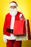 Joyous Santa posing with colorful shopping bags - stock photo
