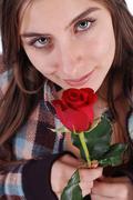 Beautiful girl smelling rose - stock photo