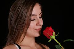 Woman smelling a red rose - stock photo