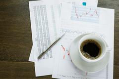 Coffice cup and financial documents Stock Photos