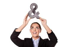 Businesswoman holding up an ampersand - stock photo