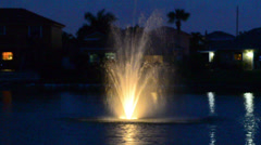 yellow iluminated fountain on the middle of a lake 01 - stock footage