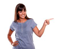 Latin young woman looking and pointing her left - stock photo