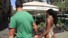 People walking by outdoor restaurant in Barcelona Stock Footage