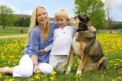 Happy mother, young child, and dog in meadow Stock Photos